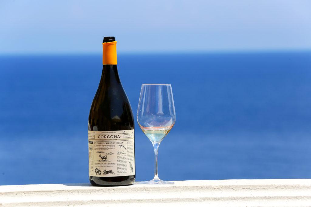 Een glas met fles Gorgona wijn aan zee