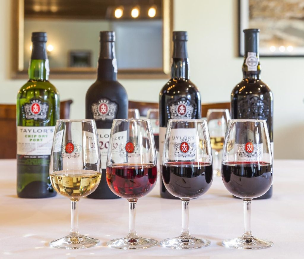 vier flessen port en glazen, alle vier verschillende van kleur