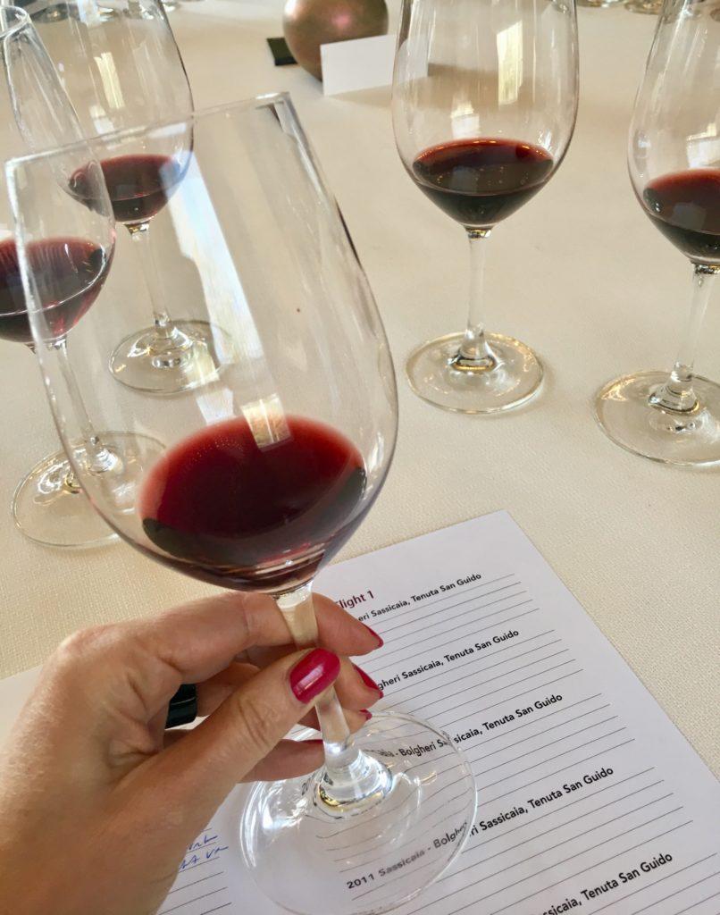 Hand met rode wijnglas